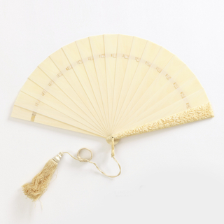 Brisé fan. Plain, unpainted and non pierced ivory sticks connected with white silk ribbon. Ivory guards elaborately carved with lilies of the valley and other flowers. Carved ivory loop. Braided silk tassel ring. Cardboard case covered with paper, lined with cerise paper.