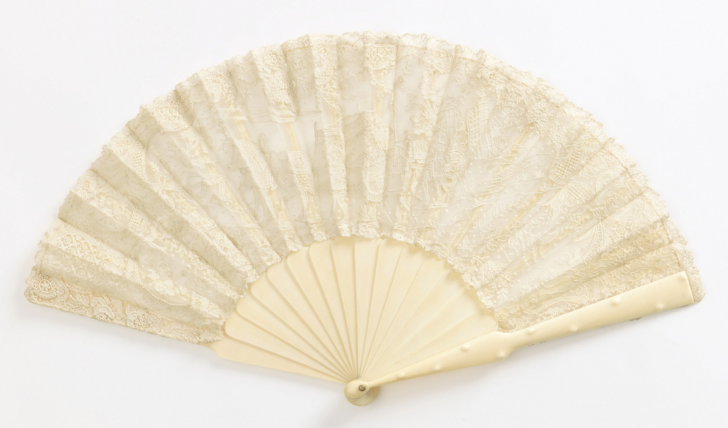 Pleated fan with needle lace leaf showing royal procession, lined with net. Ivory sticks. Guards have raised bumps in imitation of bamboo.