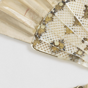 Pleated fan, Painted white satin leaf. Obverse: scattered flowers, grasses and cherry blossoms. Carved and pierced mother-of-pearl sticks applied with gold foil. White chenille tassel. Pin is set with a faceted stone.