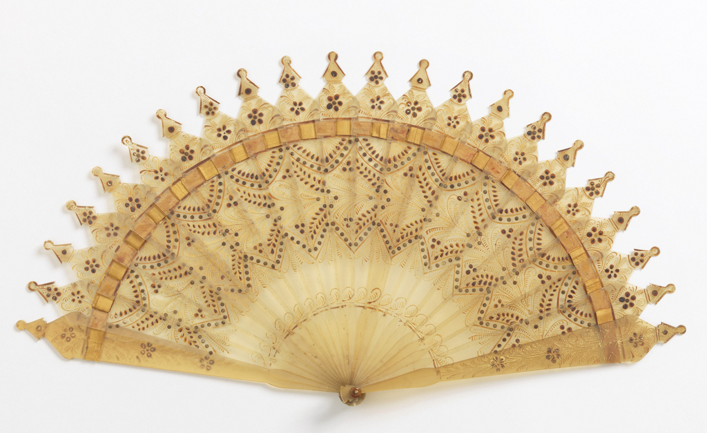 Brisé fan. Blond horn decorated on obverse with gold painting of floral, fern, wheat and feather motifs. Sticks connected by gold-colored ribbon. Steel piqués arranged in scalloped band below ribbon.