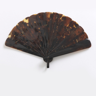 Brisé fan. tortoise shell sticks connected with brown ribbon; tortoise shell bail. In box with tan paper tooled in gilt.