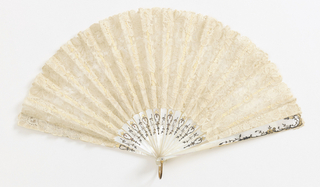 Pleated fan. White bobbin lace leaf in floral design. Incised and pierced mother-of-pearl sticks with silver and gold flowering vine design. Mother-of-pearl rivet head and gilt metal bail.