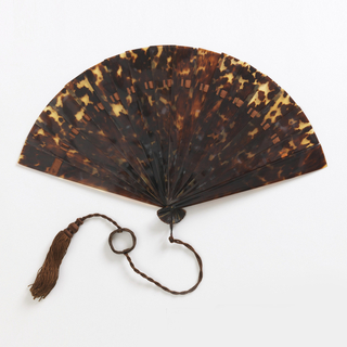 Brisé fan with tortoise shell sticks. Brown silk connecting ribbon. Black metal bail and brown silk tassel.