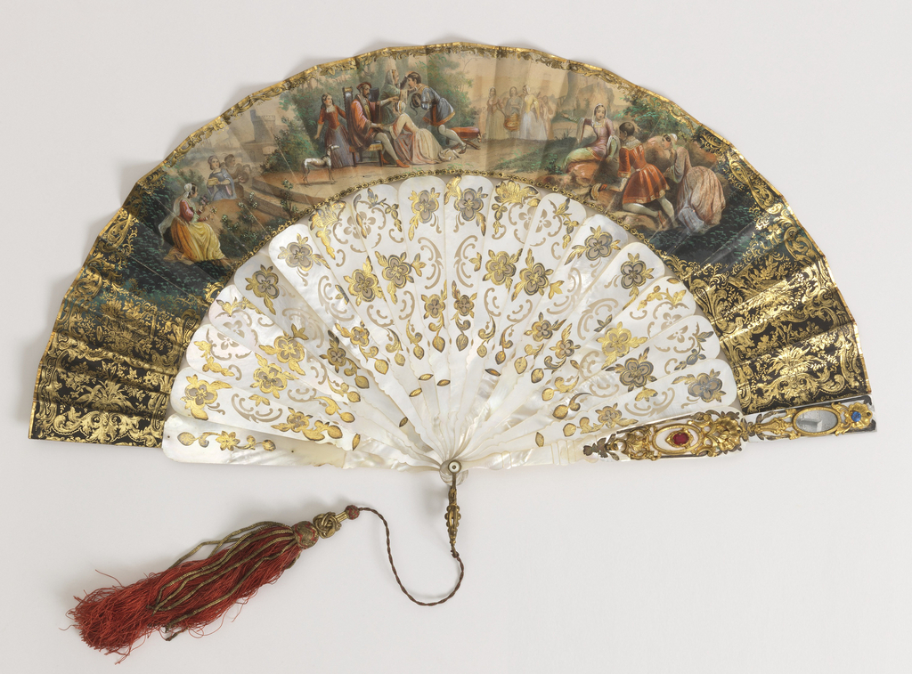 Pleated fan. Printed, hand-colored and gilded paper leaf. Obverse: a young man and woman receive blessings from a seated man and woman; groups of figures watch from the left, right and backdrop. Reverse: a pastoral scene. Pierced mother-of-pearl sticks with gold foil. Gilded metal plaque, mirrors and faceted glass stones on guards. Gilt metal bail and silk tassel with metal threads.