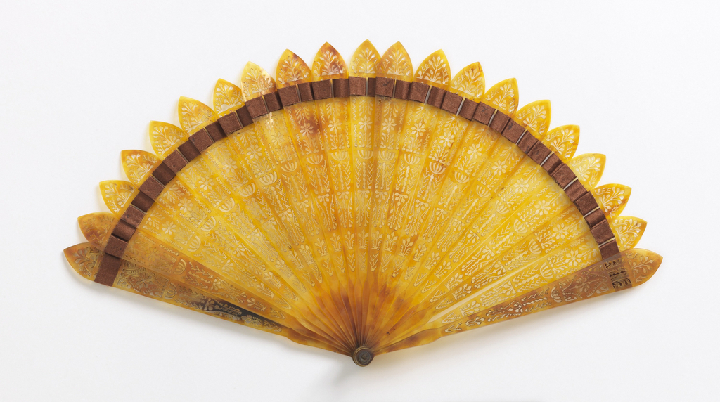 Brisé fan. Pierced tortoise shell sticks with brown silk connecting ribbon.