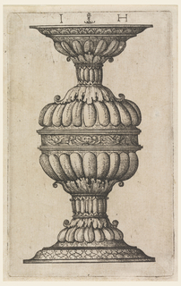 Vertical rectangle showing a double goblet decorated with gadrooning and acanthus leaves. At center, a mask. At the base, an interlaced design.
