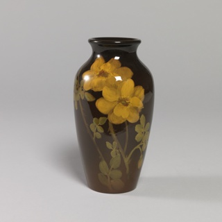 Elongated ovoid footless body, short neck, flaring lip. Two yellow flowers, buds and green leaves painted on brown ground under brilliant glaze. Yellow Interior.