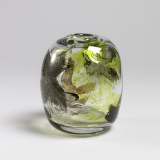 Narrow-mouthed vase of clear, yellow, and green glass with air bubbles and wire mesh inclusions.