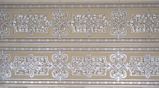 C-scrolls alternating with rectangles containing scrolls. Beaded framed borders. Printed in white on tan ground.