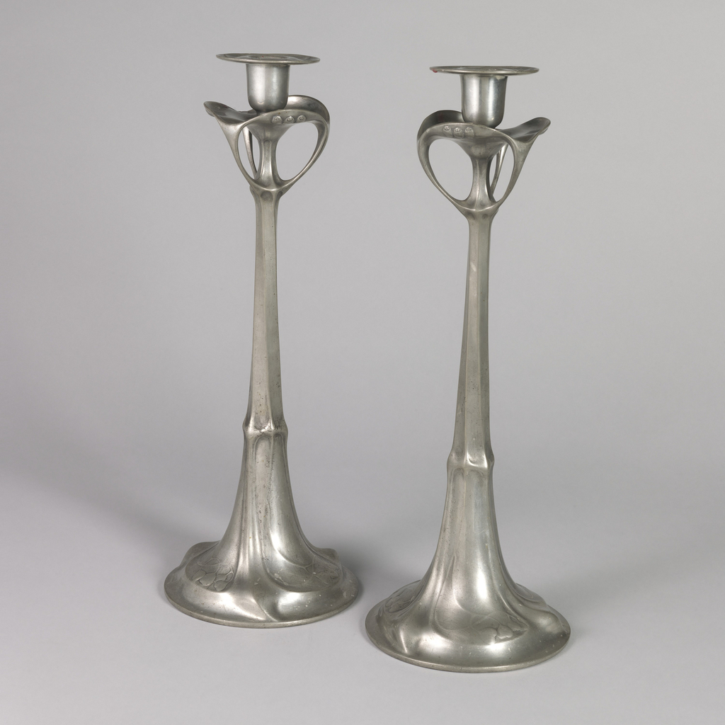 tall with  loops below the drip pans, on flared foot with curvilinear flowing fabric-like raised decoration