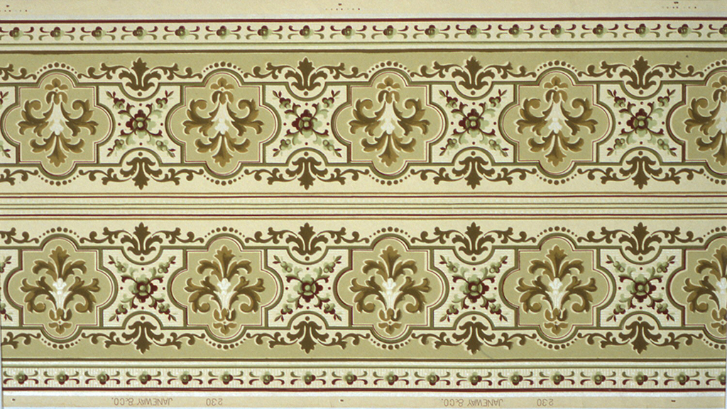"""Borders printed two across. Wide central band of interlocking geometric shapes (puzzle-like), each containing stylized foliate motif, bordered by dot and floral motifs. Top has white mica beading, dark red stripe, green tan stripe. Bottom has band of green and red floral motif in between two sets of multicolored stripes. Ground is beige. Printed in shades of brown, green and tan on off-white ground.  Printed in selvedge: """"Janeway Co. 230"""""""