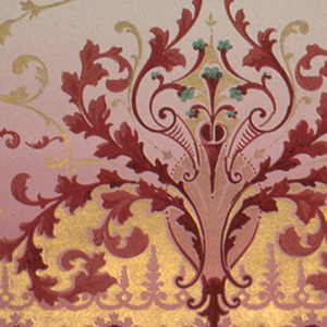 Scrolling medallions, alternating between larger and smaller. Printed in burgundy and metallic gold on background that shades from tan to red.
