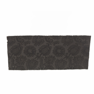 Black-on-black silk fragment of flower and leaf shapes arranged diagonally.
