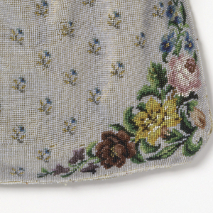 Large purse of linen embroidered overall with gray beads with floral designs in many colors in teh corners. Silver clasp inscribed Aus Vaterlichen Liebe Zum Andenken 1821 (With fatherly love, souvenir of 1821). The bag is not lined, revealing the many colored silk threads used to attach the beads to the linen ground.