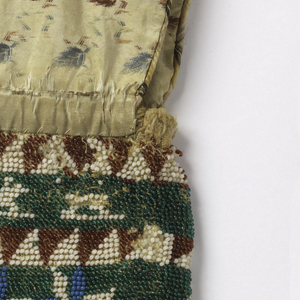 Small bag fringed with blue beads and topped with fold-over flap of patterned brocaded taffeta. Rows of simple designs of stars, flowers, dogs. The name Sally Exnights? and Watersbourough, 1837 are worked into the embroidery.