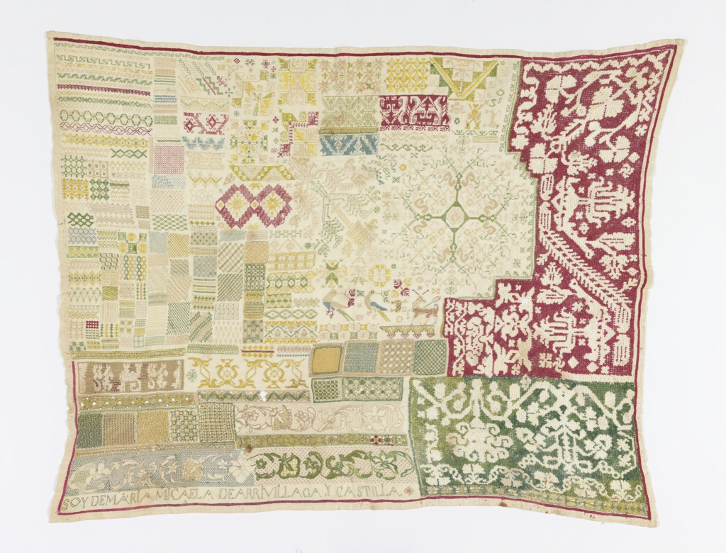 Rectangular sampler with many small bands and squares of geometric patterns, in blues, greens, yellows, pinks and reds on white. The right side is dominated by two large areas of deflected element work in red and green.