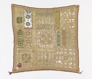 Square sampler comprised of rectangular and square compartments containing circular motifs. Some circles are embellished with blue, green, dark yellow or red thread.