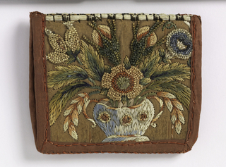 Two stiff pieces of bark, hinged and edged with red cotton and embroidered with colored straw in a floral design.