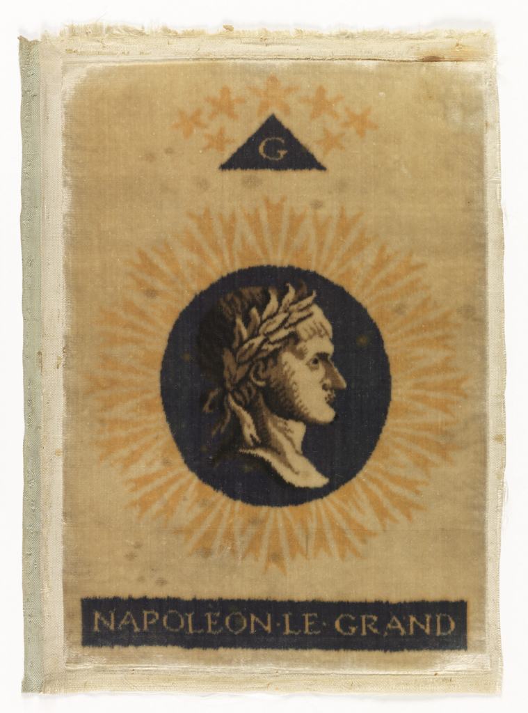 """Small panel of cut silk velvet printed with a portrait in profile of Napoleon I within a dark blue circle surrounded by orange rays against a white ground. Below center medallion in a dark blue band appears """"Napoleon Le Grand."""" At top is a triangle in dark blue with the initial """"G,"""" surmounted by seven stars."""