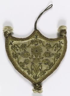 Flat, shield-shaped pendant of white satin embroidered in gold and sequins. The pattern, identical on both sides, represents a monstrance with sprays of wheat at the sides, and a border of floral scrolls. Silk tufts at three corners. Loop of gold cord to hang.