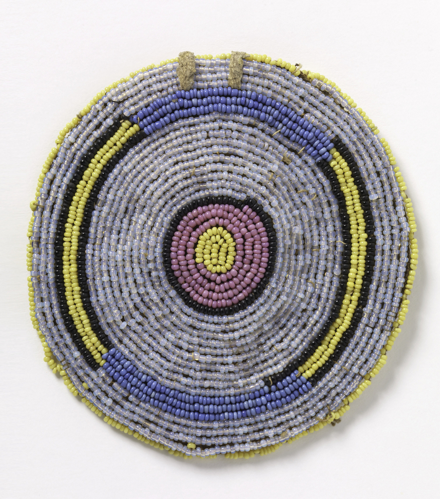 Circular pendant in a design of concentric circles worked in seed beads of yellow, blue, light blue, pink and black.