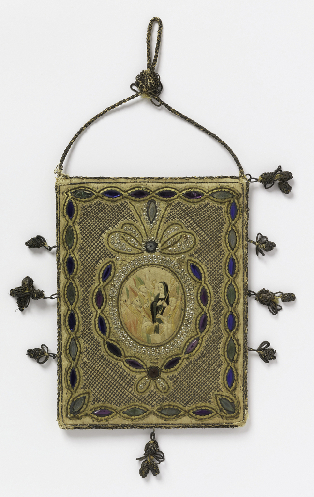 A scapular decorated with embroidery. On one side the Annunciation and on the other a small medallion with a female saint surrounded by bishops. Metallic cord and tassels. Colored glass beads.