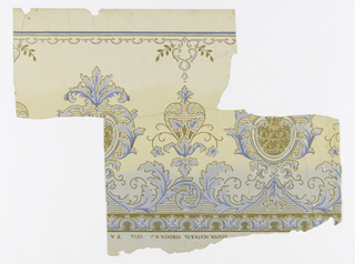 Foliate bandings, shield-like ornaments in shades of blue, metallic silver and gold, outlined in mica-like gold. Frieze shades from light blue at bottom to light salmon color to tan at top. Flitter frieze
