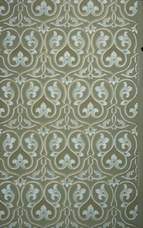 On dark gray ground, white scrollwork with gold beaded frame.