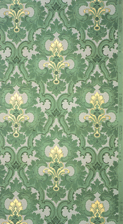 On speckled white-gray ground, treillage in green scrolls with motifs in gold and green in shapes of acanthus leaves and foliage.