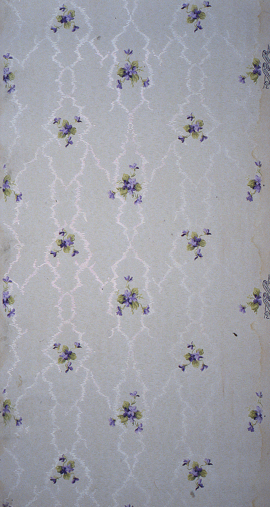 On light gray ground, treillage in white composed of small horizontal stripes representing moire, with small clusters of purple and green flowers and leaves.