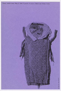 Hand-made, rough doll printed in black on purple paper.  She wears a head scarf from which waist-length hair escapes.  She has three teeth and lays with her arms raised.