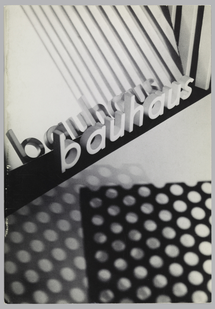 "Bauhaus exhibition catalogue or Ex Libris. Vertical format, black and white abstract photoillustration fills the cover. Shadows cast by a material perforated with circular holes at bottom create rows of white dots. At upper right, an intersection of diagonal lines. At center, two groups of three-dimensional letters placed on a surface spelling ""bauhaus"" in black and white diagonally across composition. Inside, text and images relating to 197 items in the exhibition at Elaine Lustig Cohen's gallery, Ex Libris."