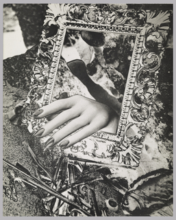 Exhibition catalogue for Dada and Surrealism. Vertical format, black and white surrealist photoillustration fills front cover. A female hand with polished nails reaches through an empty ornate picture frame against an abstract ground made up of various images in photomontage style. Partial image of a fish at lower right. Inside,text and images relating to 521 items in the exhibition. Verso: photoillustration of a hand holding a pocket watch.
