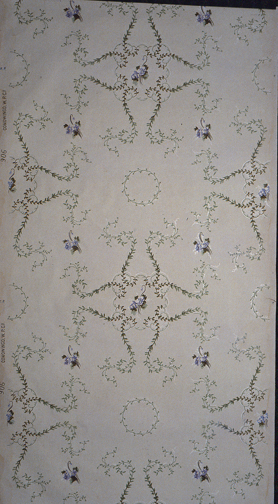 On gray ground, green rinceaux in scroll form with clusters of purple flowers throughout.