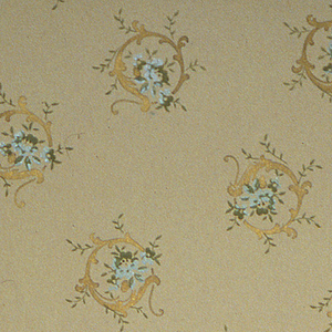 On light brown ground, staggered C-scrolls in gold containing clusters of light blue flowers.
