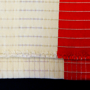 Sample woven in shades of off-white and red showing multiple patterns of grids and lines.