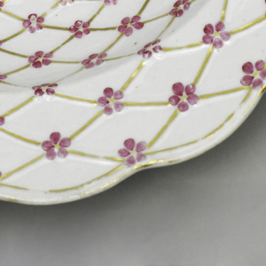 Circular form with scalloped rim; white ground decorated overall with molded and gilded trellis pattern with small pink blossoms with yellow centers at crossing points.