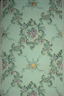 """Treillage pattern of pink and green floral vining, with bouquets and foliate scrolls. Ground is light green and embossed in a grid-like pattern. Printed in pinks, greens and gold mica.  Printed in selvedge: """"Imperial Wallpaper Co. Sandy Hill. N. Y. 992"""""""