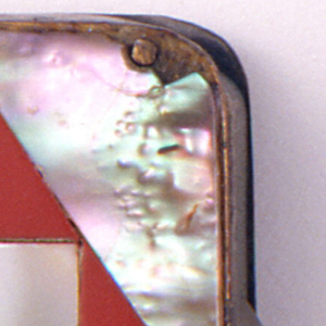 Rectangular, one long side curved like the back spine of a book, with faux tortoise cut and wrapped around form, front and reverse decorated with mother-of-pearl-pieces at four corners, which surround large red plastic diamond shape with rectangular mother-of-pearl piece at its center, all cut and adhered to metal body of box. Thin, flat, recessed lid opens by depressing button and side panel situated on long metal side, below hinge. Striker in recessed groove on bottom.