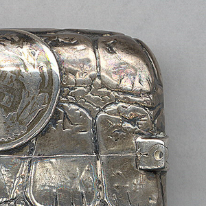 Oblong, rounded corners and sides, featuring an overall ground of simulated alligator skin, on top of which are superimposed silver coins; front features quarter dollar coin on lower right, with American eagle, inscribed United States of America, smaller coin on lid at upper left with worn image of a seated Lady Liberty, dated 1853 below; reverse features larger coin on lower right with image of a seated Lady Liberty, dated 1877 below, small dime on lid at upper left. Lid hinged on side. Striker on bottom