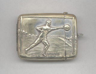 """Rectangular, image/text reads horizontally, featuring raised decoration of British football player in mid-stride on playing field, reaching towards a thrown ball, inscribed below right """"Saved"""", identical on reverse. Link attached to lid top. Lid hinged on long side, thumb catch on opposite side. Striker on bottom."""