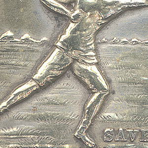 "Rectangular, image/text reads horizontally, featuring raised decoration of British football player in mid-stride on playing field, reaching towards a thrown ball, inscribed below right ""Saved"", identical on reverse. Link attached to lid top. Lid hinged on long side, thumb catch on opposite side. Striker on bottom."
