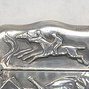 Oblong, with curved sides and corners, featuring raised decoration representing a variety of vices, including woman in profile smoking, the cigarette smoke extending up and around parts of the background, at bottom is long serpent, above on left are playing cards, at center champagne bottle, at right a champagne glass, on lid are 2 racing horses, identical decoration on reverse. Lid hinged on side. Striker on bottom.