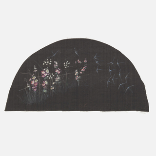 Black fan leaf painted with gouache showing flowers and fireflies.