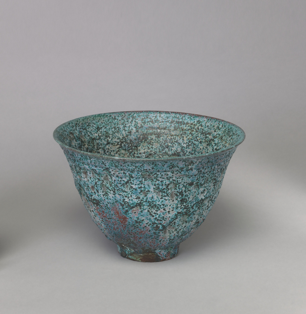 Footed and flared bowl decorated in speckled colors of turquoise, black, and tan.