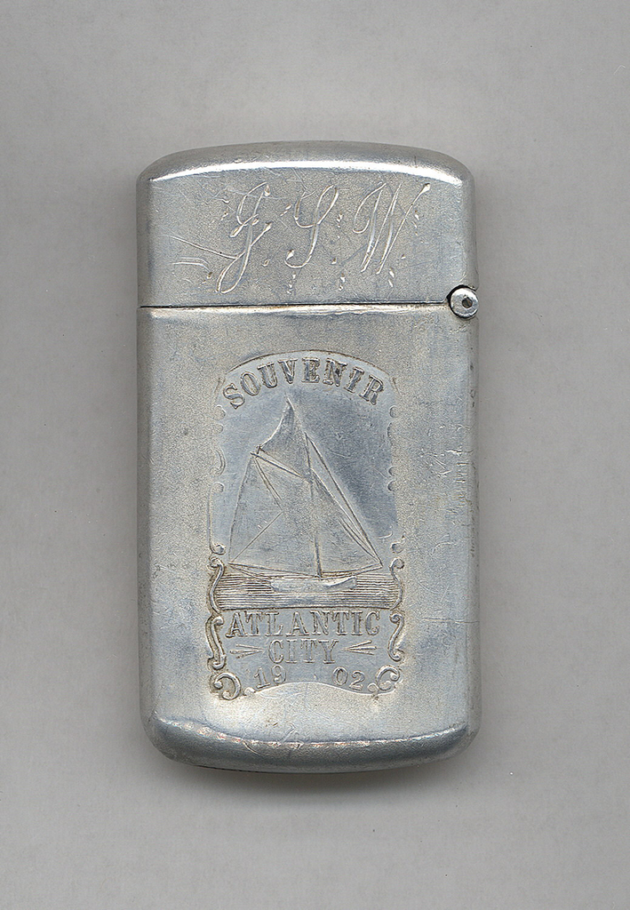 """Rectangular, curved sides, top, and bottom, featuring raised decoration of sail boat on water, inscribed above """"Souvenir"""" and below """"Atlantic City, 1902"""", all framed by c-scrolls and s-scrolls, incised initials J.G.W. on lid; reverse features incised leaf motif. Lid hinged on side. Striker on bottom."""