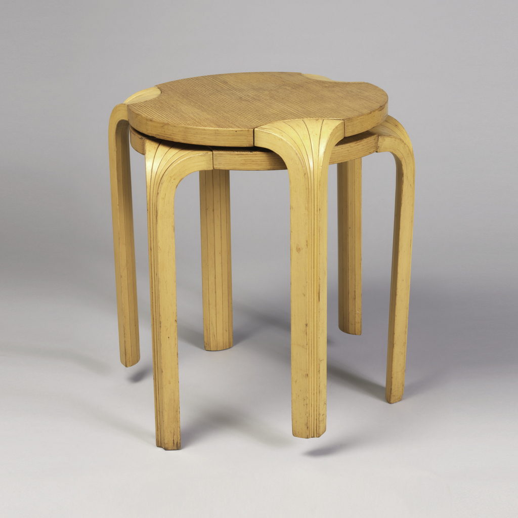 Pair of stacking stools, each with circular wooden seat with three slender concave ribbed legs composed of laminated vertical wood strips curved at knee.