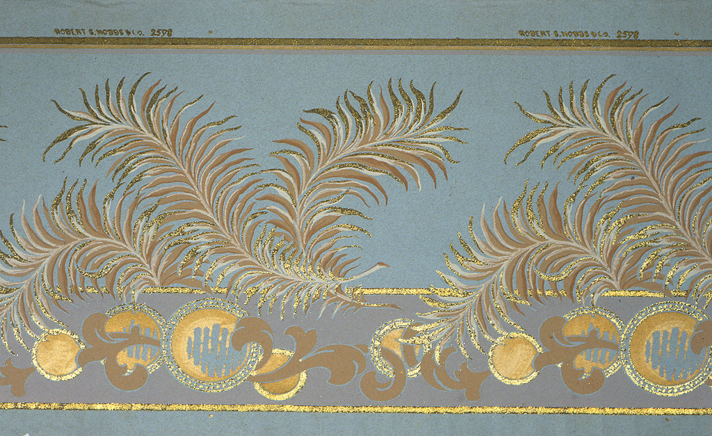 Flitter frieze, with wide central band of large-scale scrolling feathers or ferns, with scrolling acanthus and circles below. Printed in tan, brown, metallic gold and mica flakes on blue-gray background.