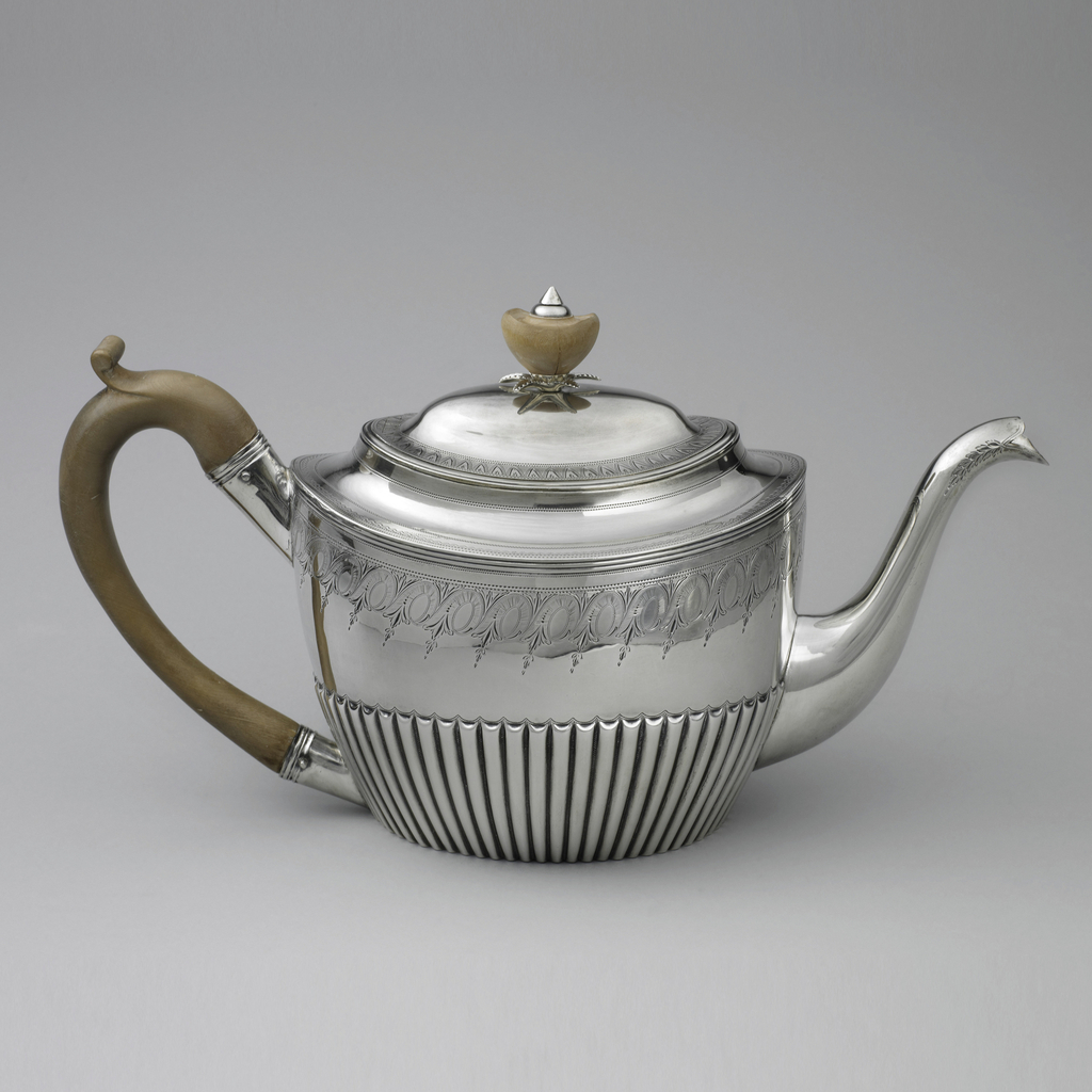 Silver teapot engraved with a foliate and spiral patterned band at the shoulder, above a tapering reeded base; curved spout; curved wooden handle; slightly domed lid with wooden finial of smooth acorn shape topped with silver terminus, its base with silver leaf form surround.