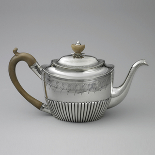 Silver teapot with tapered and fluted base curved spout, wooden curved handle, engraved body with foliate and spiral pattern; wooden finial and smooth acorn shape topped with metal and base with leaf-like forms.